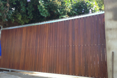 Wooden-sliding-gate-with-vertical-slats-and-a-steel-frame-with-spikes-3