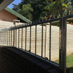 Steel Pedestrian Gate Installed With A Panel On Top Of A Wall