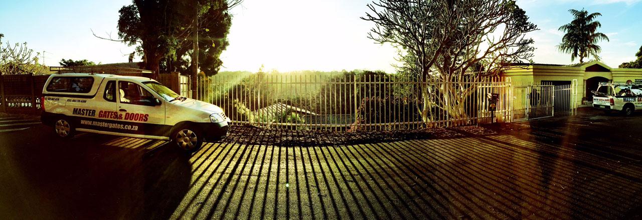 Master Gates Branded Car Next To Palisade Fencing