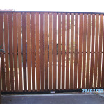 Wooden Sliding Gate With Vertical Slats And A Black Frame