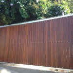 Wooden Sliding Gate With Vertical Slats And A Steel Frame With Spikes