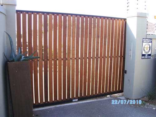 Balau Wooden Sliding Gate With Vertical Slats And A Black Frame