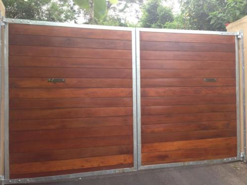 Wooden Swing Gates With Horizontal Slats And A Steel Frame